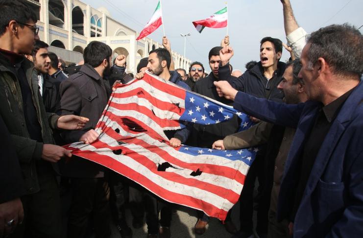 Iranianos rasgando bandeira dos EUA por conta do tratado de armamento