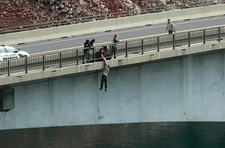 Policial heroico agarra o braço do homem suicida enquanto ele se balança na ponte da Califórnia